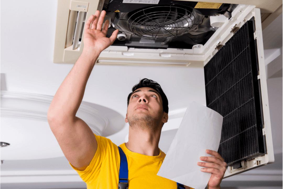 contractor repairing ceiling air vent consulting manual