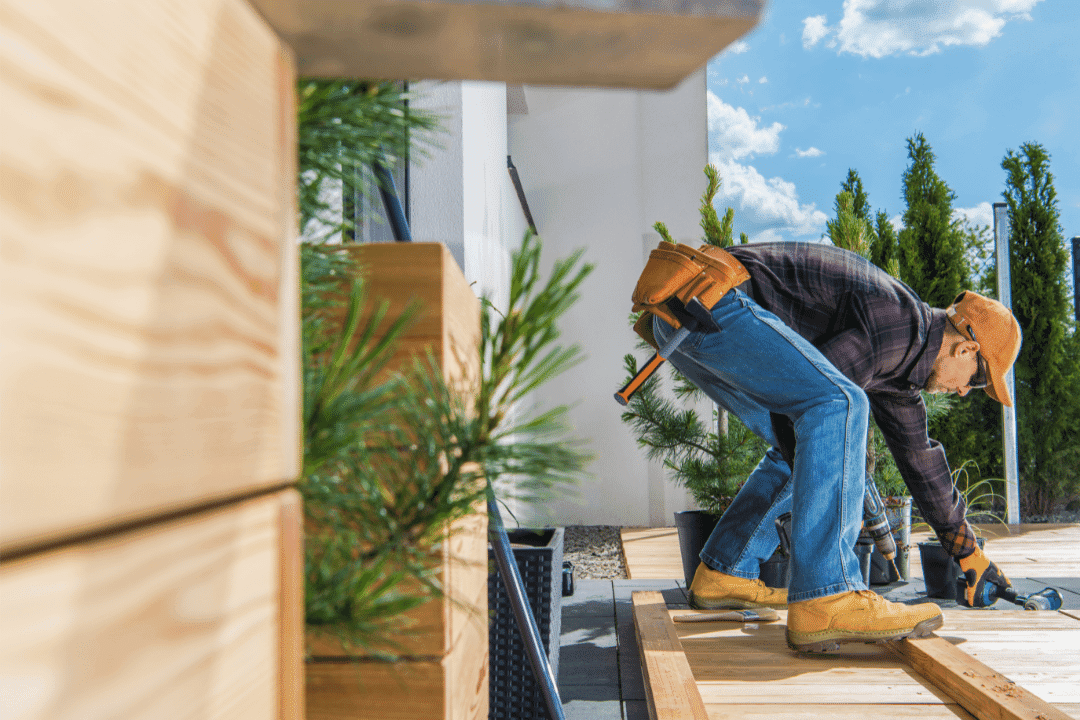 repairman working outside installing wooden deck
