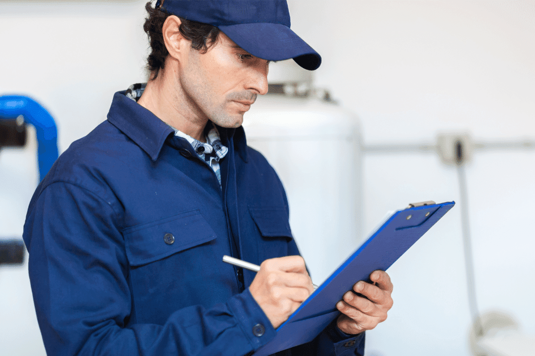 contractor looking intently at a clipboard and writing down notes