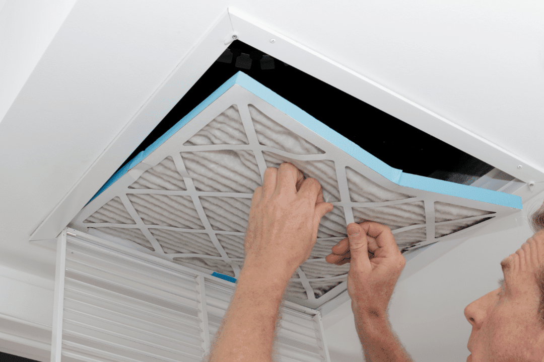man replacing dirty air filter in the ceiling of home