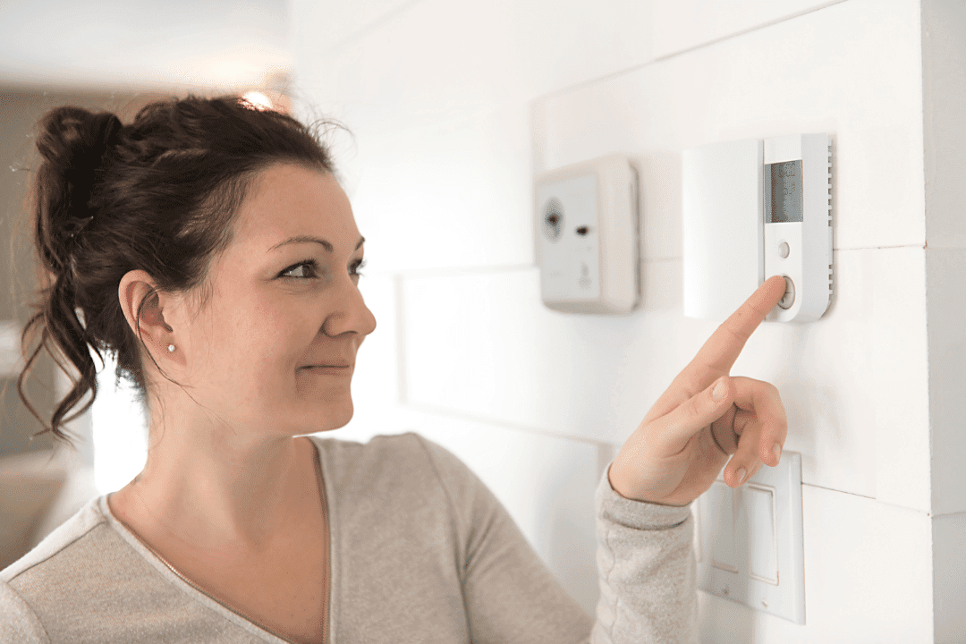 woman checking thermostat on wall digital