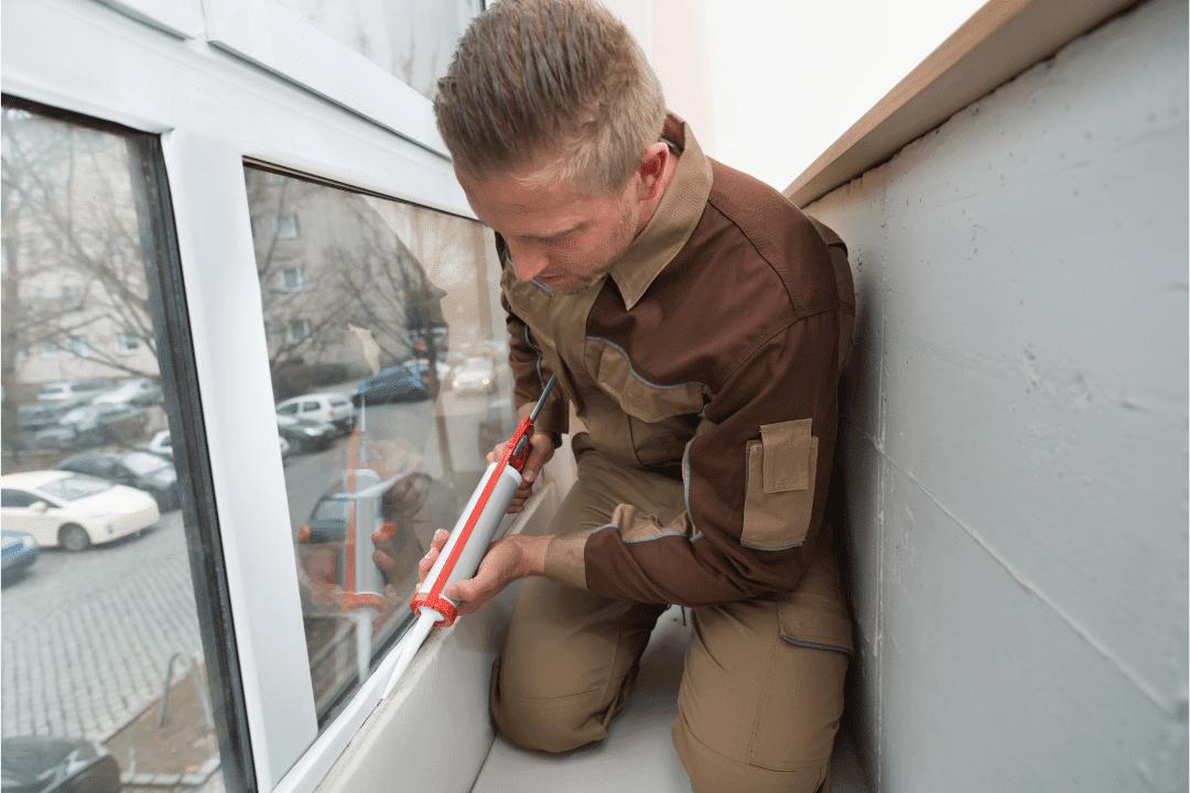 worker applies silicone glue caulk to window in home