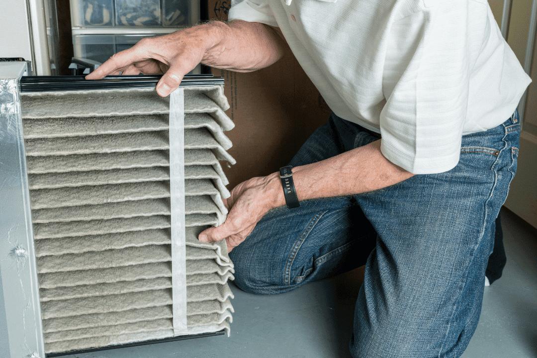 older man replacing dirty air filter in furnace