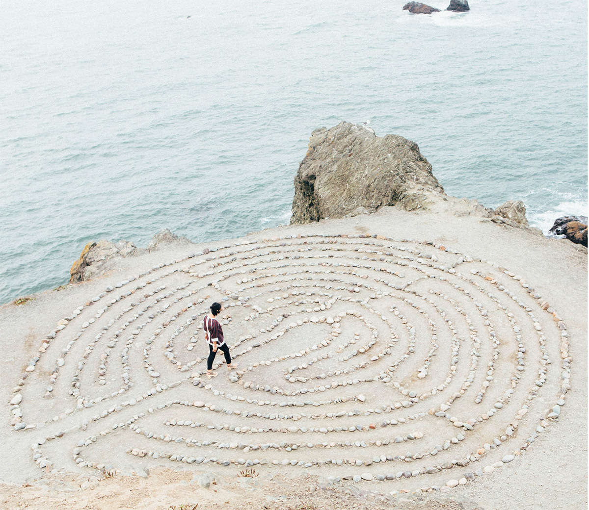 Maze of rocks on the beach with a woman finding the center
