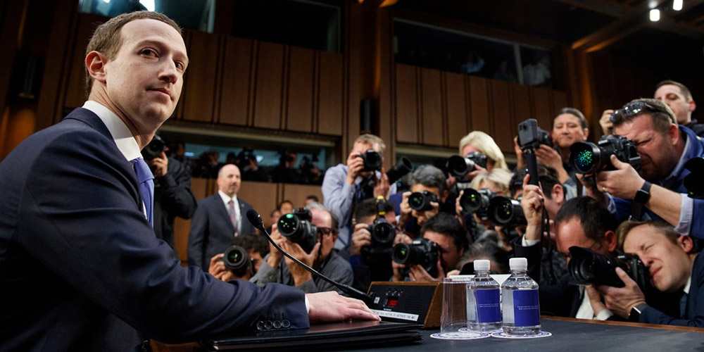 Mark Zuckerberg looking at the camera with reporters surrounding him