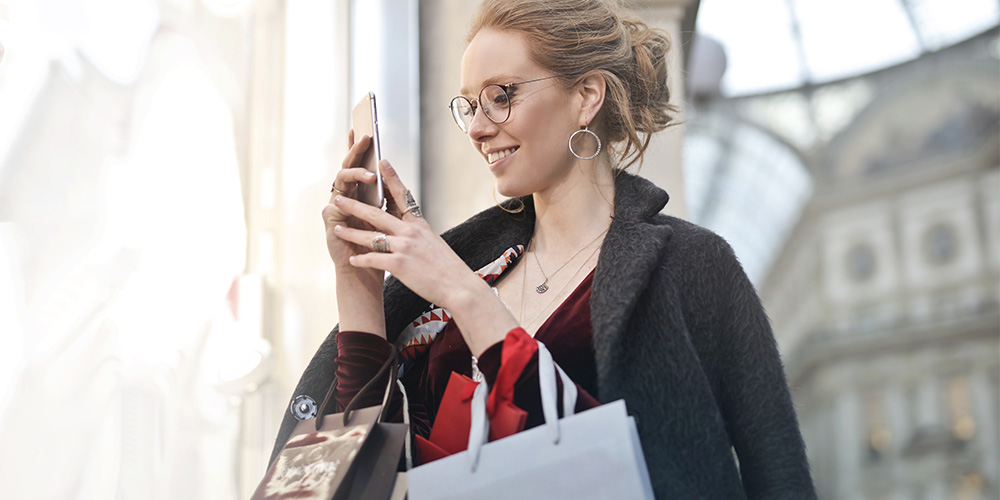 Woman with shopping bags using her phone