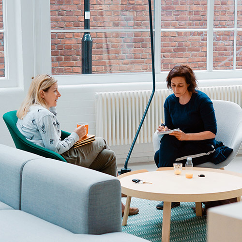 Two women sitting in round chairs sitting around a table discussing work.