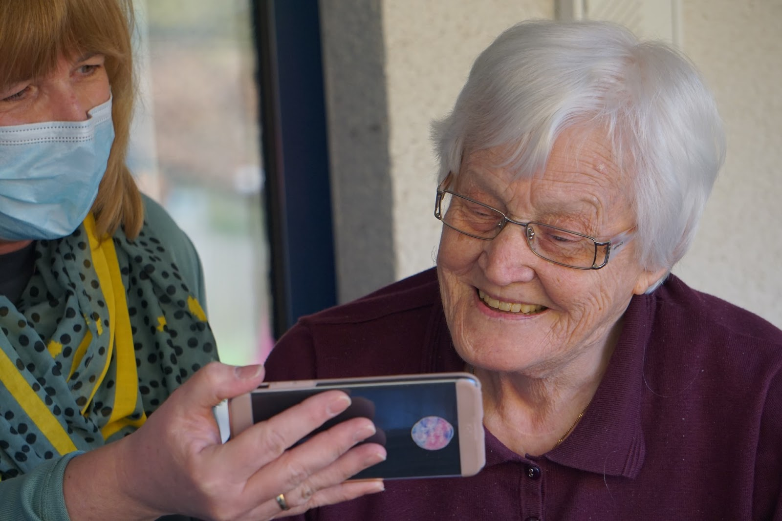 healthcare worker showing elderly worker something on her cell phone