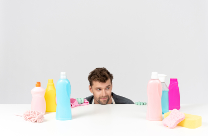 young-man-sitting-at-the-table-and-looking-sadly-on-all-cleaning-tools
