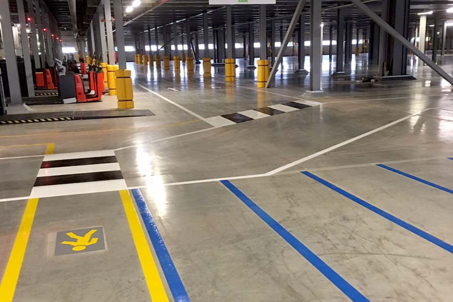 Photograph of warehouse safety floor markings and barriers.