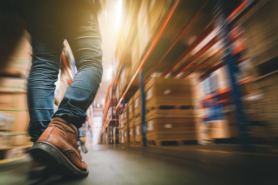 Man walking through a warehouse facility with motion blur.