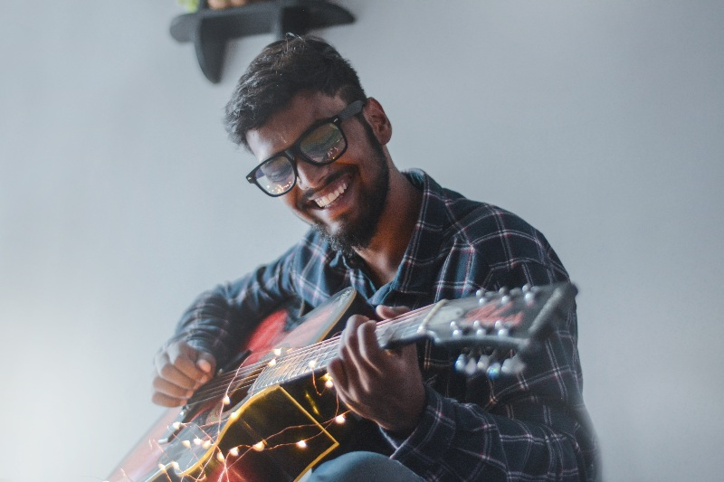 man playing guitar smiling