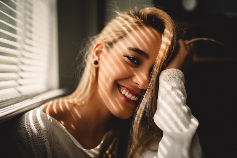 woman smiling holding hair