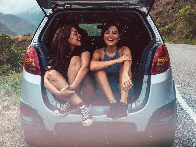 women sitting in tailgate of car laughing