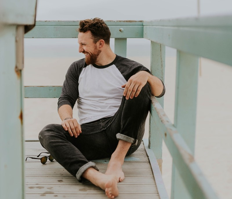 man sitting on dock smiling