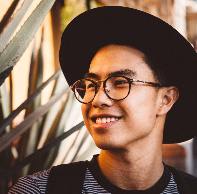 man with hat and glasses smiling
