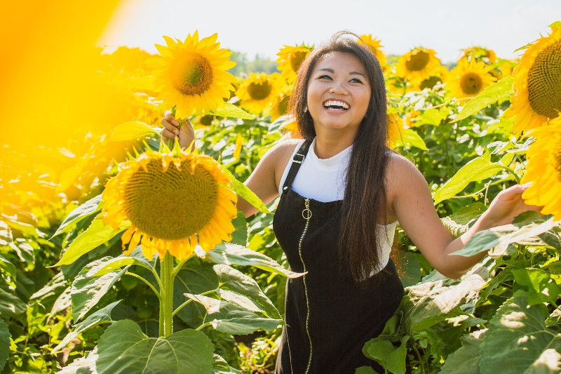 woman smiling near sun flowers