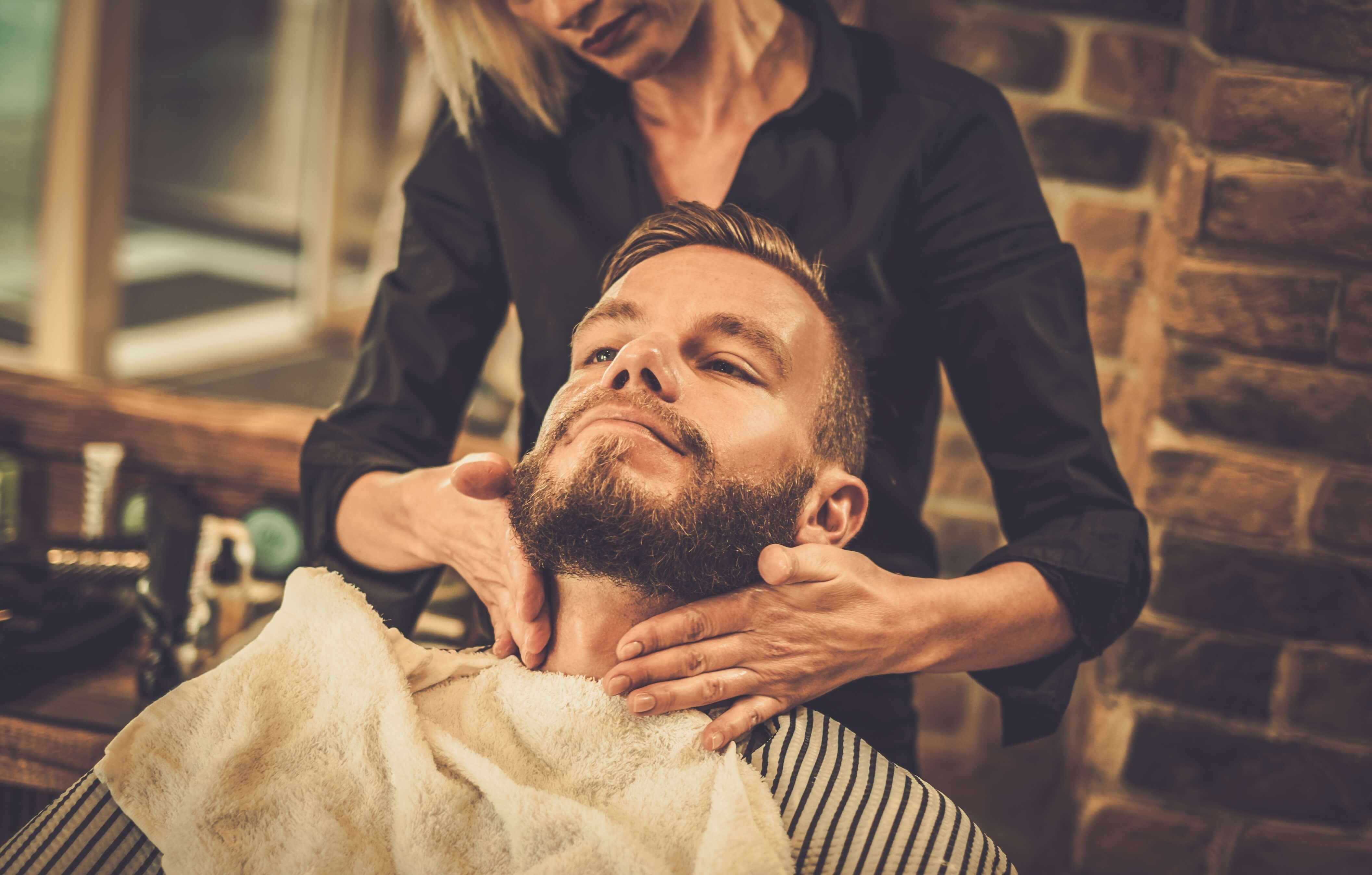 A man getting his beard groomedby a woman.