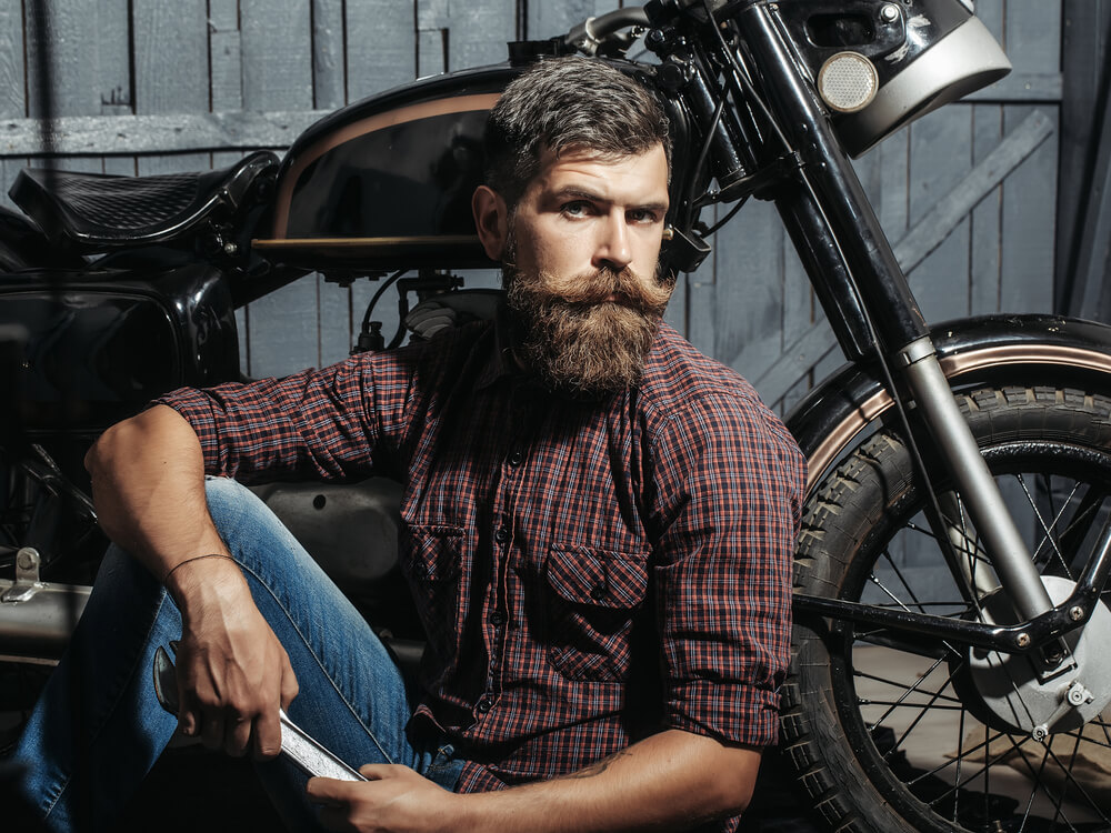 A man with a huge beard sitting in front of a motocycle.