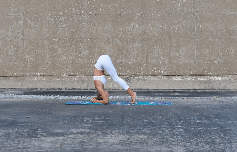 Shift your weight forward for the third step of doing a headstand.