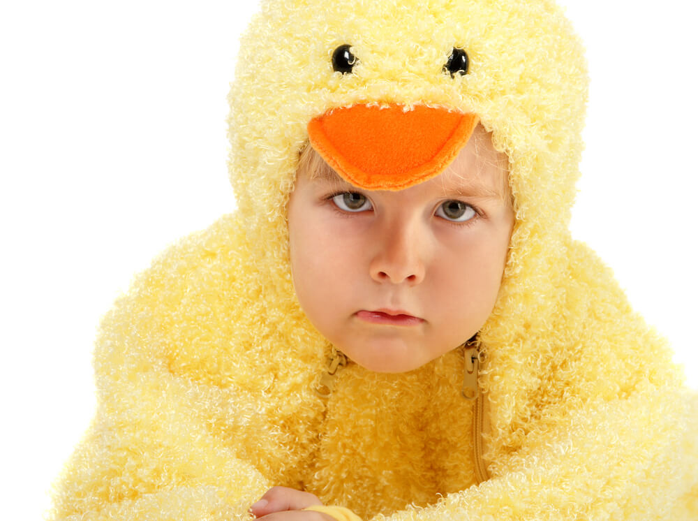 A young child in a chicken costume looking disappointed.