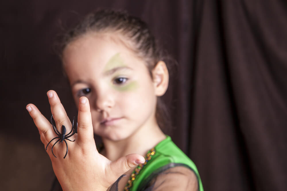 A young girl with a plastic spider ring on her finger.