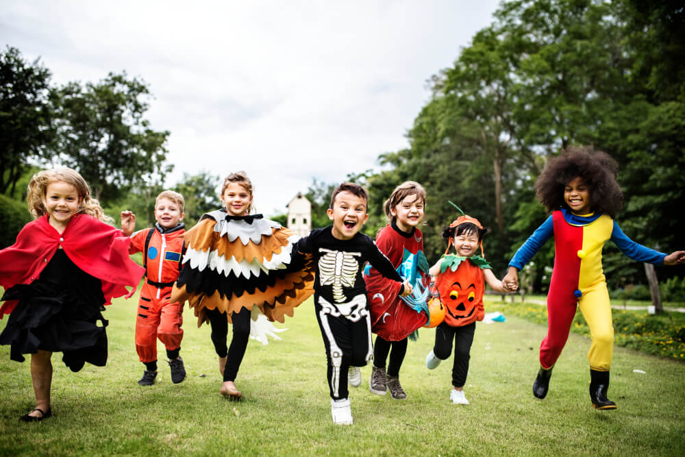 A group of children running towards the camera with Halloween costumes on.