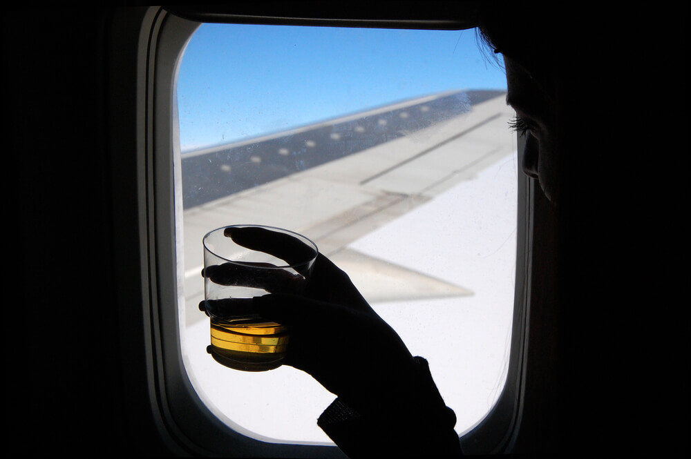 A person drinking alcohol on a plane.