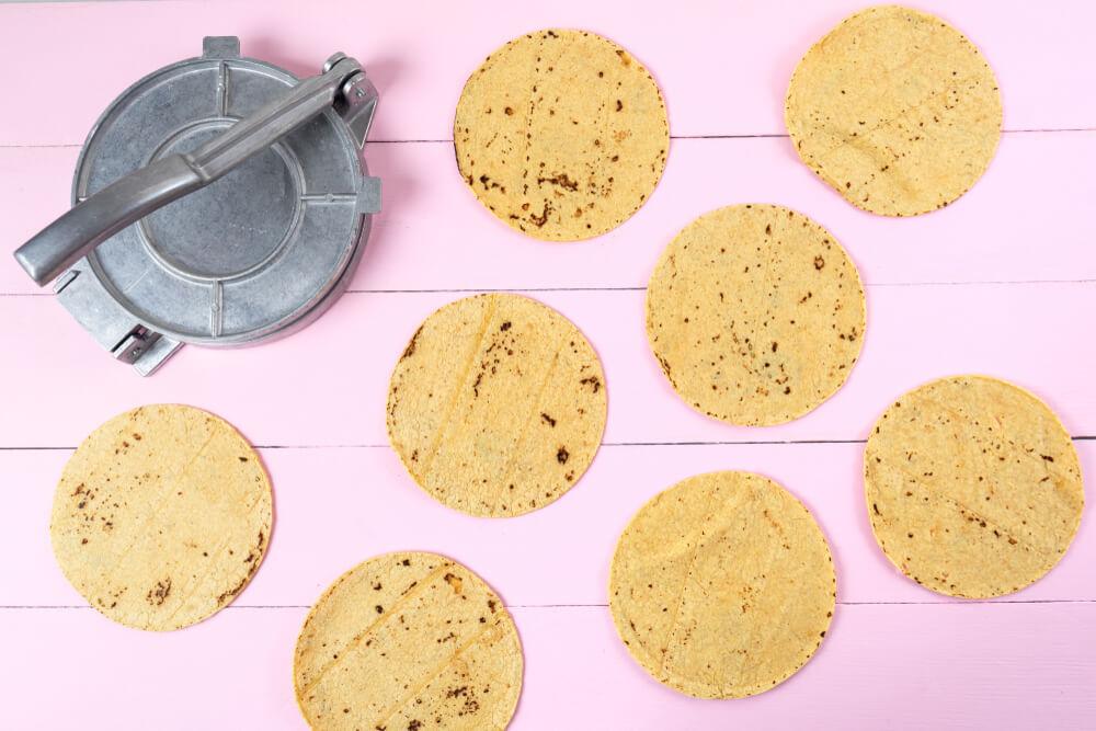 A tortilla press and a few tortillas.
