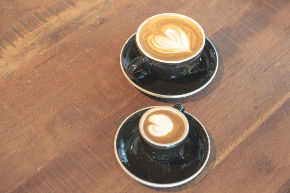Two coffee drinks on a wooden table.
