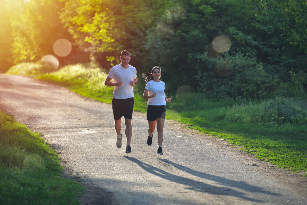 A man and a woman running on a country road.