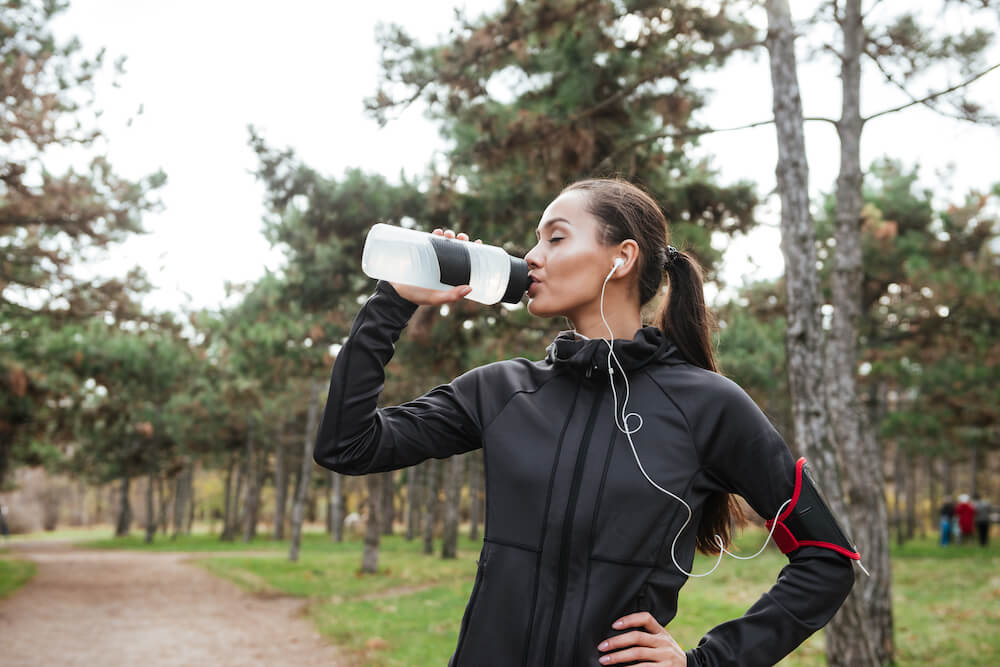 A woman drinking from a water bottle.