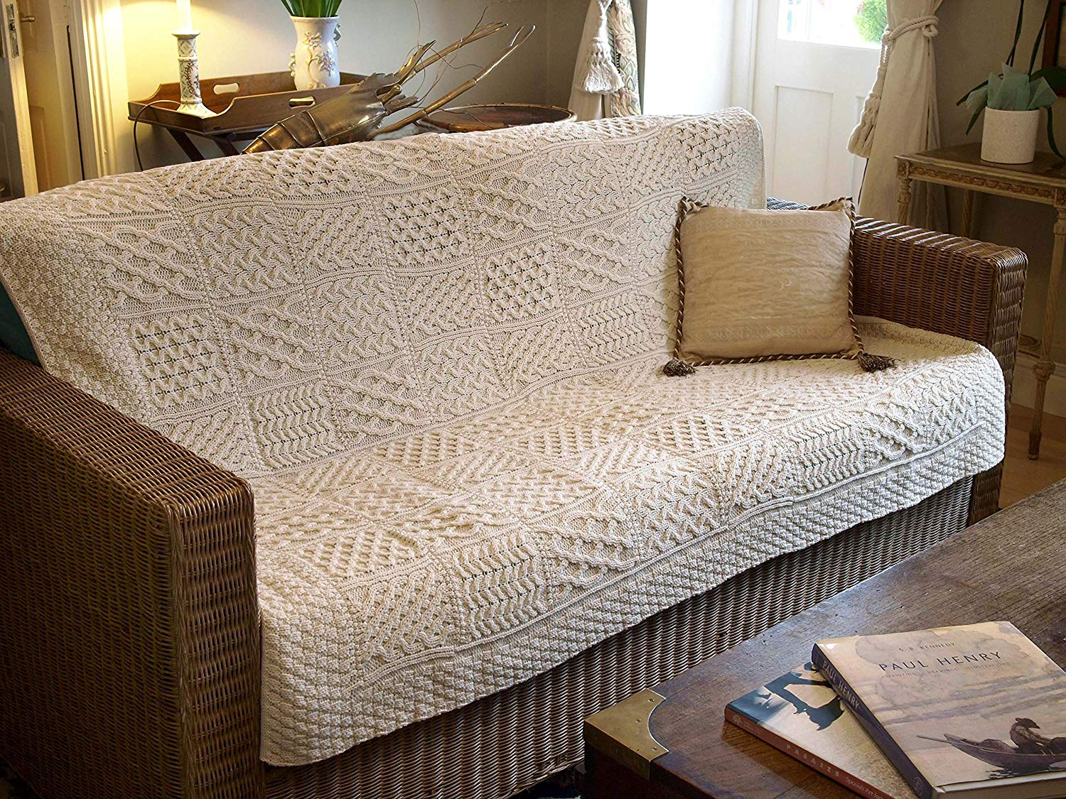 A couch with a large knit blanket on it.