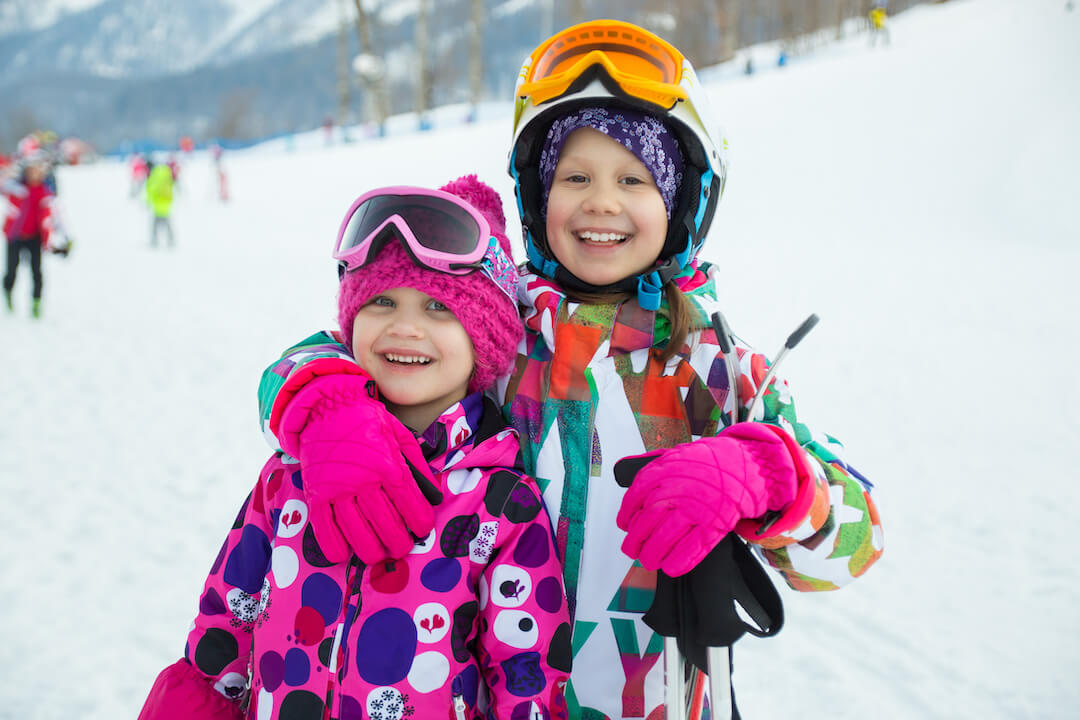 Two kids smiling in all of their ski gear.