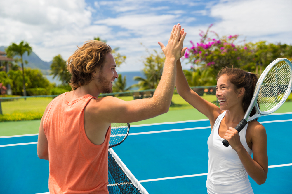 A man and woman high-fiving over a tennis net.