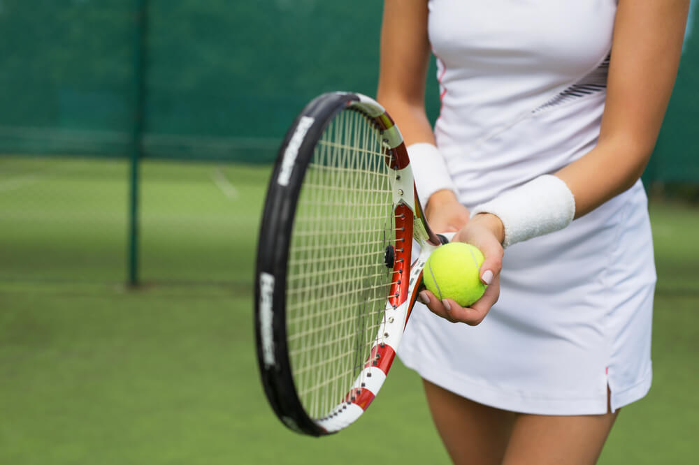 A woman holding a tennis ball and racket.