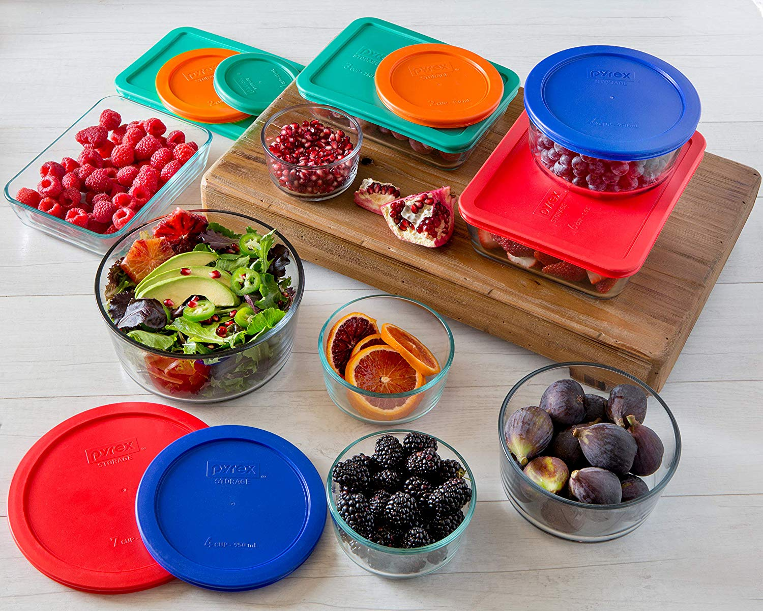 A large set of Pyrex containers filled with fruit.
