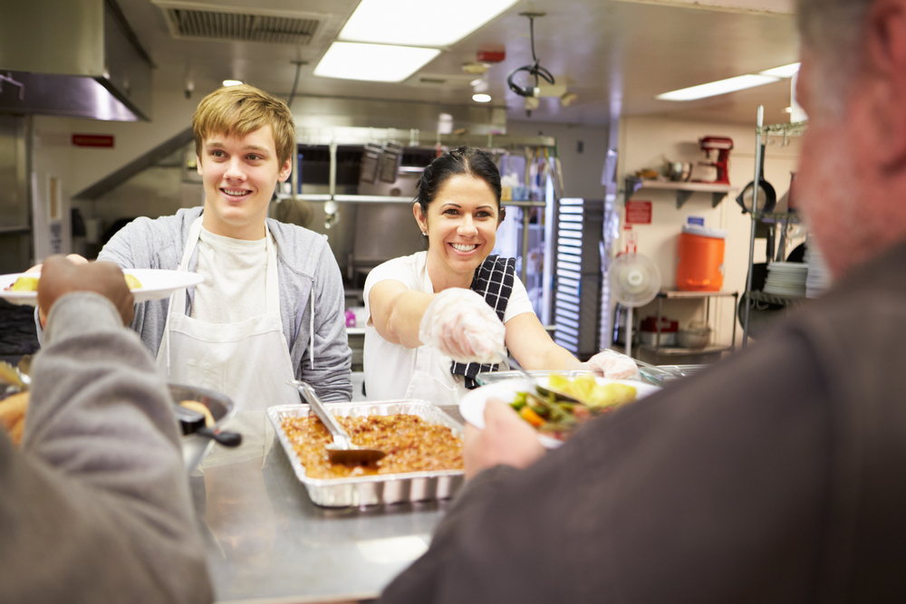 Two people serving meals at a food kitchen.