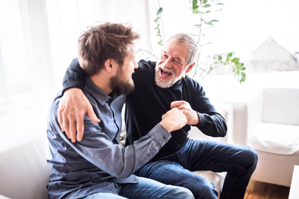 A senior citizen and a young man laughing together.