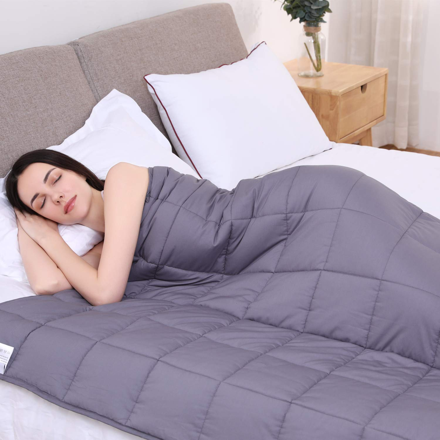 A woman sleeping with a weighted blanket.