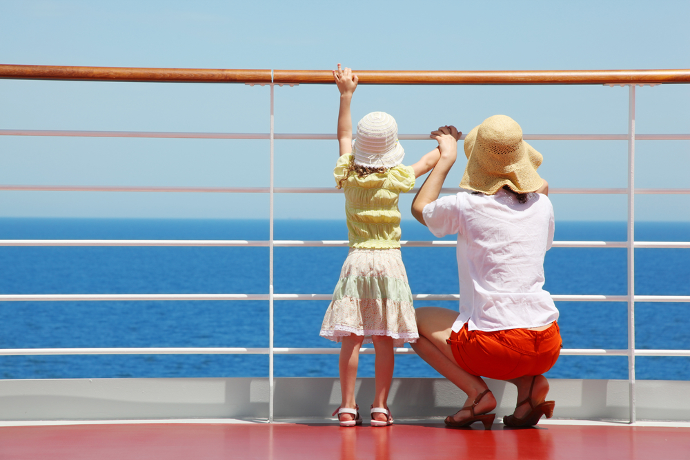 A mom and daughter looking off of the side of a cruise ship.