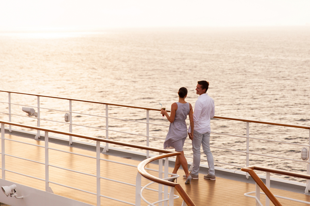 A couple dressed in white on a cruise as the sun sets.