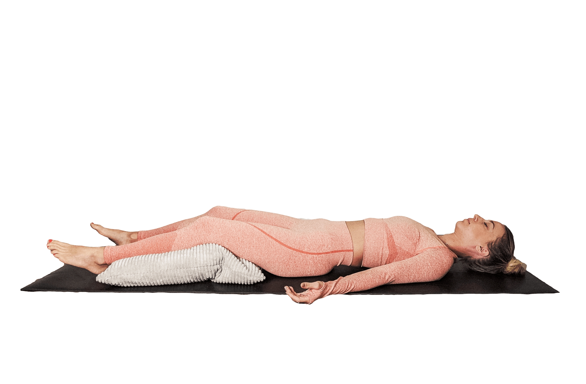 SUPPORTED SAVASANA. Lie on your back with a pillow resting underneath your knees and your arms comfortably by your sides.