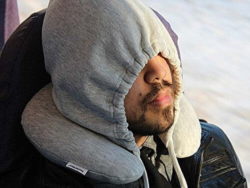 A man sleeping with travel pillow that as a hood.