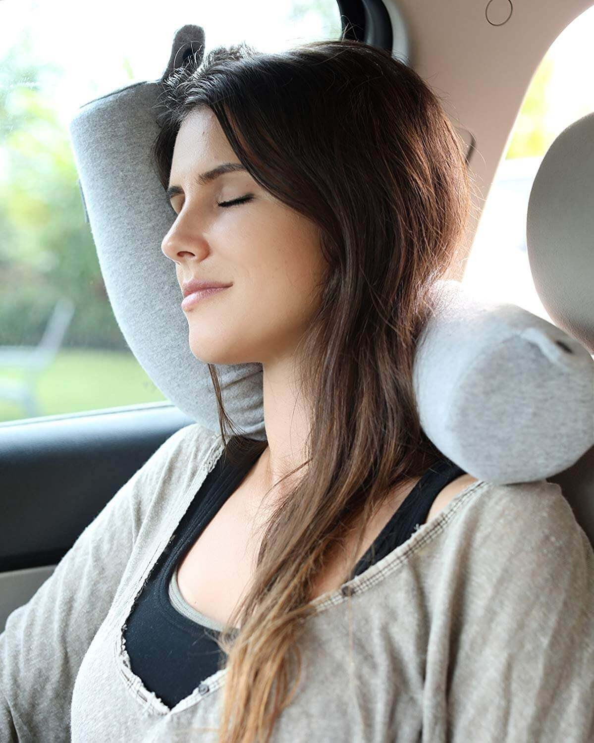 A woman sleeping in a car with an adjustable travel pillow.