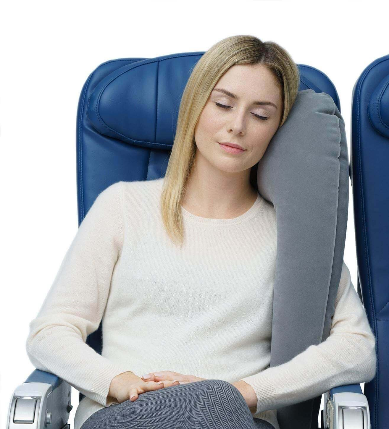 A woman sleeping on a plane with a full body pillow.