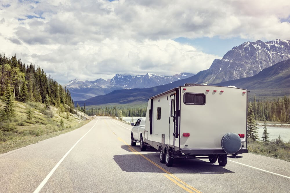RV driving down the highway with the mountains and a river beside them.