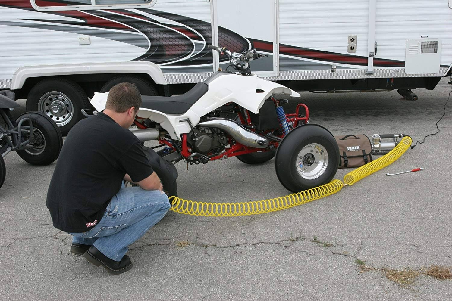 Person in front of an RV putting air into the tires of a white ATV