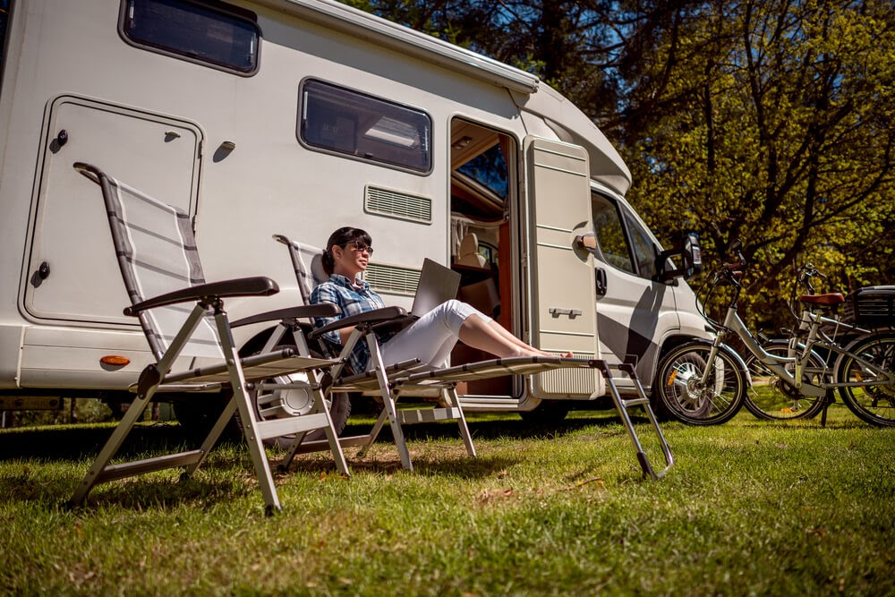 Woman in front of RV sitting in a camp chair working on a laptop.