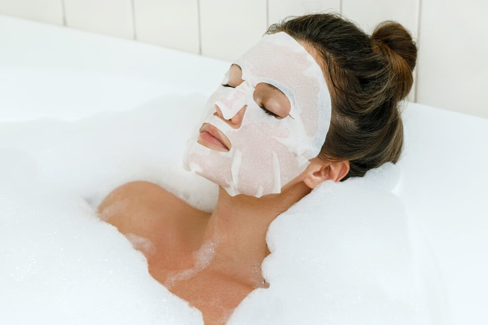 Woman enjoying a bubble bath with a face mask